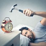 Man Hitting Alarm Clock With A Hammer As He Tries To Sleep