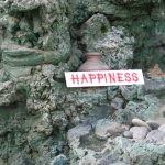 The Word Happiness Printed On White Background Among Some Grey Rocks Stones And Pottery