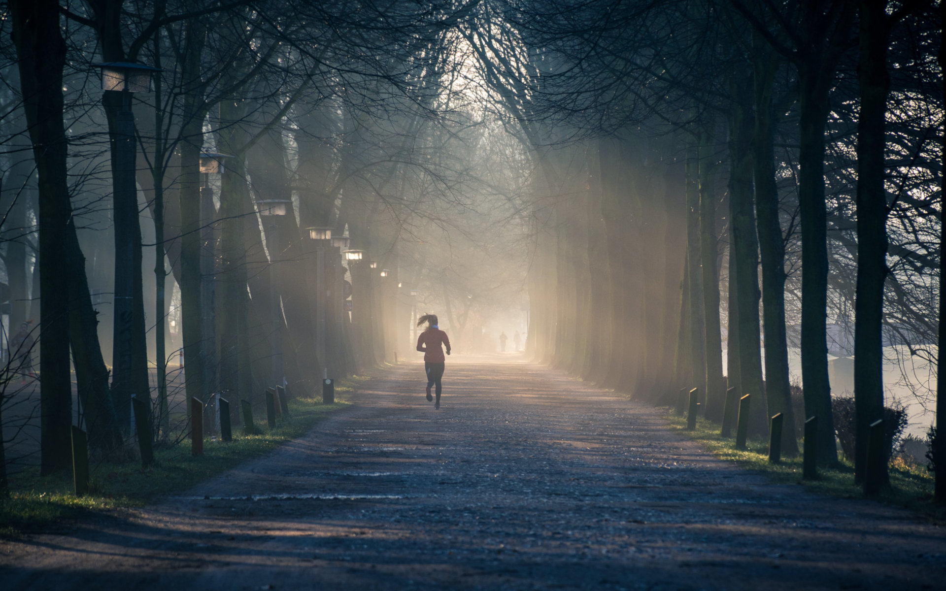 Woman Jogging Down A Dirt Road On A Winter Sunny Morning