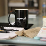 Office Desk With Papers, Pens And A Coffee Mug With The Caption Wework