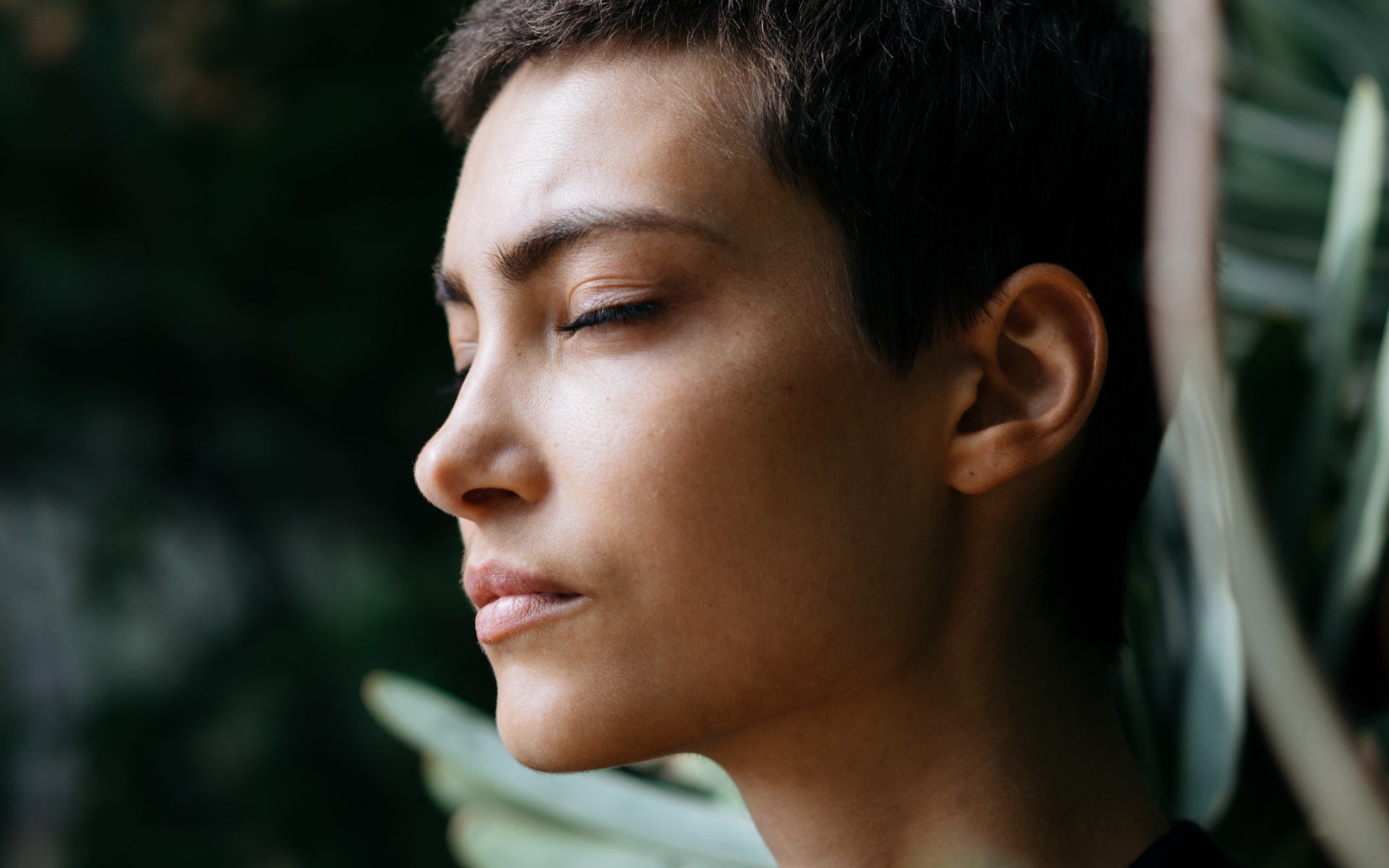 Woman In Front Of Green Tree With Her Eyes Closed In Deep Thought