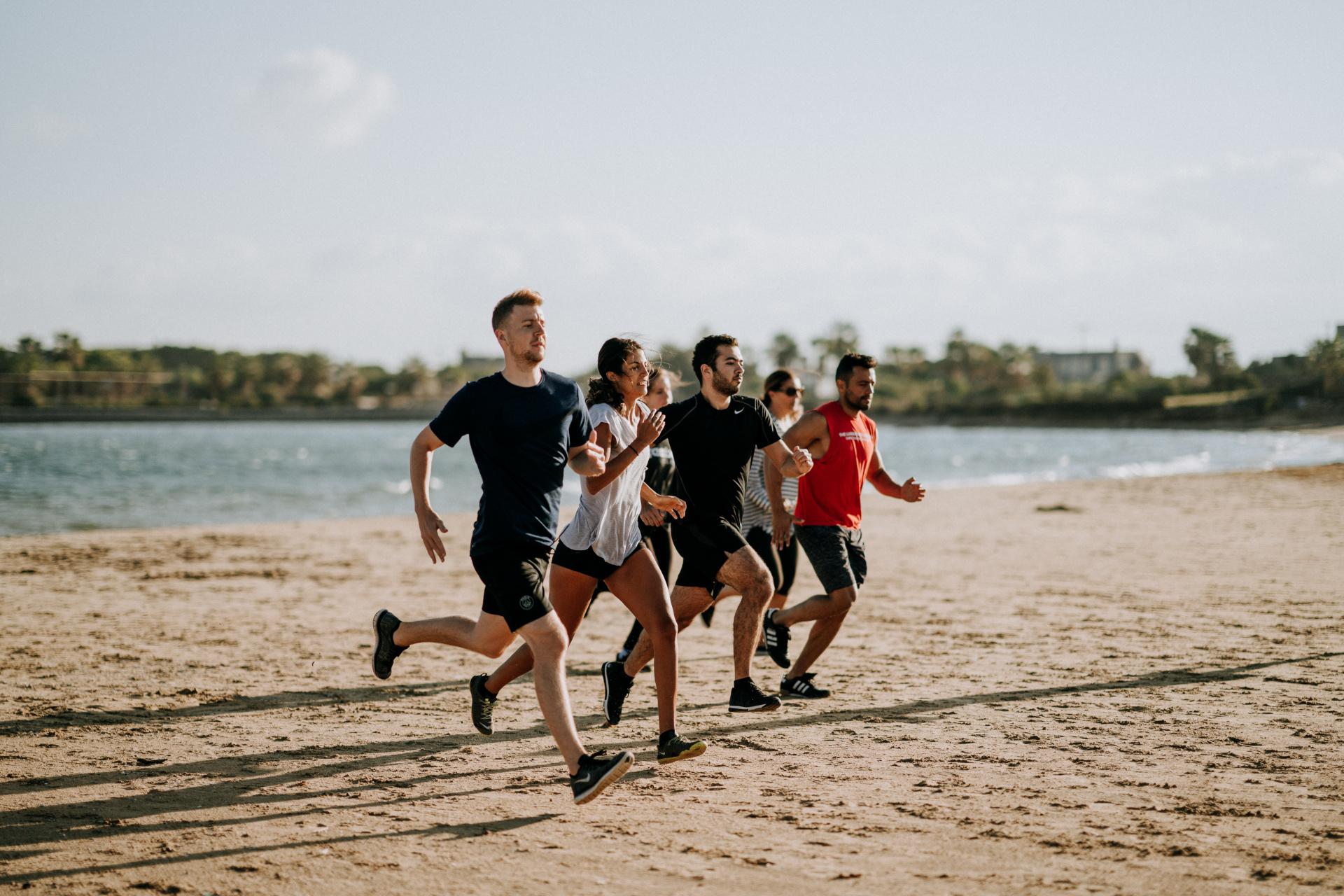 Men And Women Running On A Beach