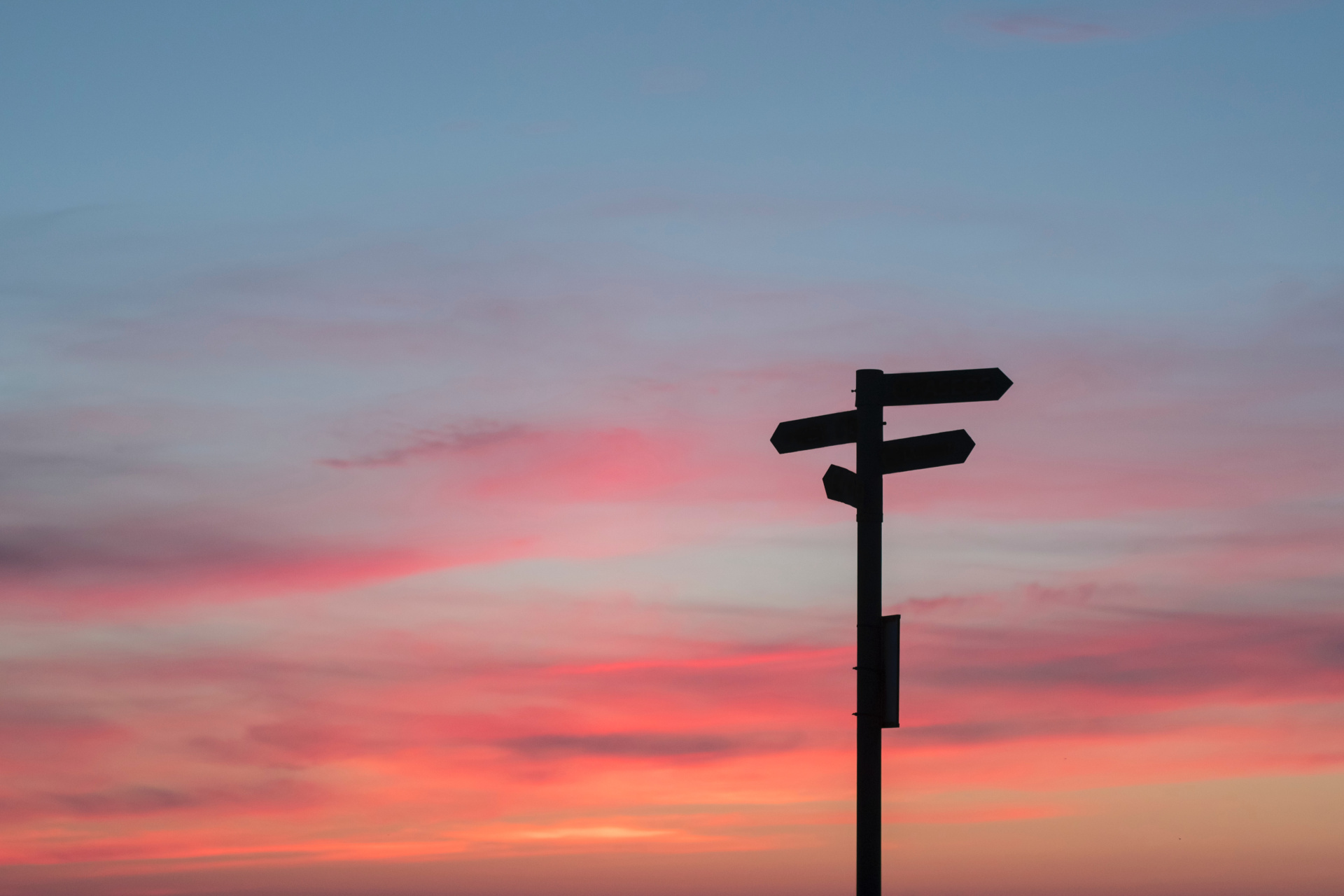 Silhouette Of Sign Post On Red Sky